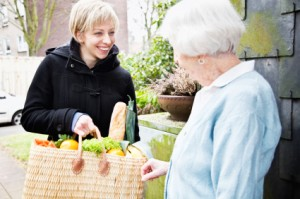 young-caregiver-bringing-purchases-to-senior-woman